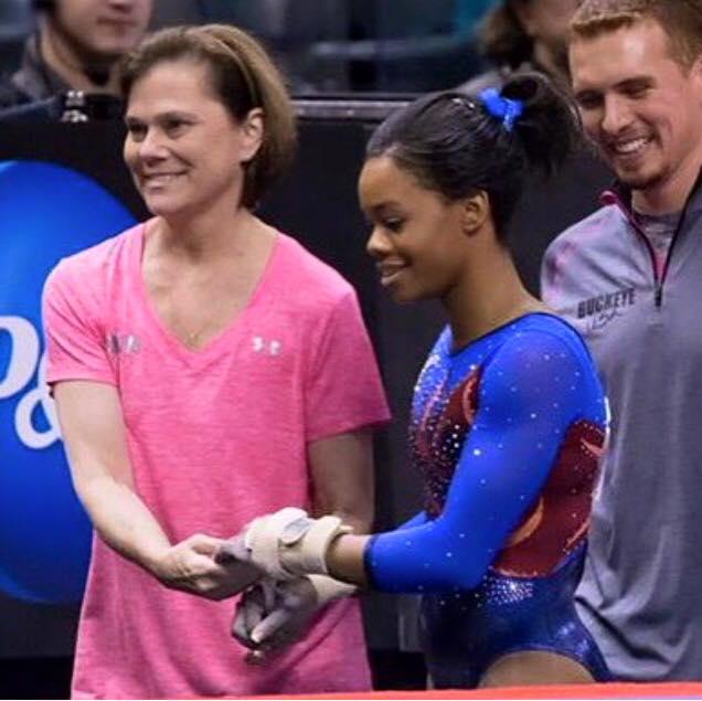 Buckeye Gymnastics coaches Kittia Carpenter and Christian Gallardo congratulate Gabby Douglas after a solid performance at the USA Gymnastics P&G Championships.